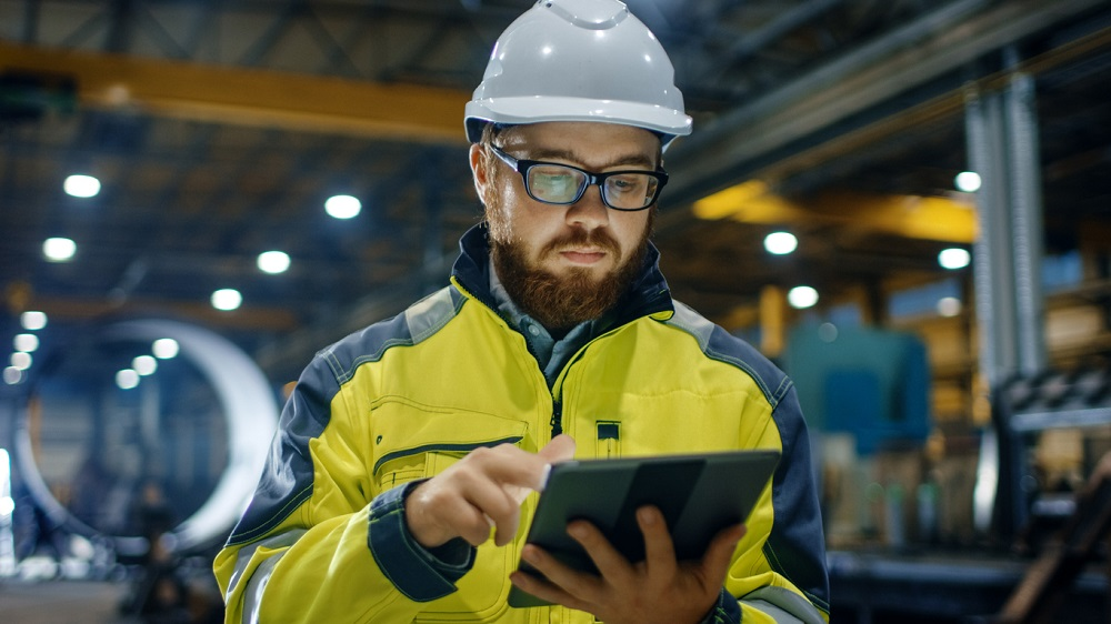 Industrial Engineer in Hard Hat Wearing Safety Jacket Uses Touchscreen Tablet Computer. He Works at the Heavy Industry Manufacturing Factory.