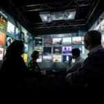 People watching multiple screens in a dark room